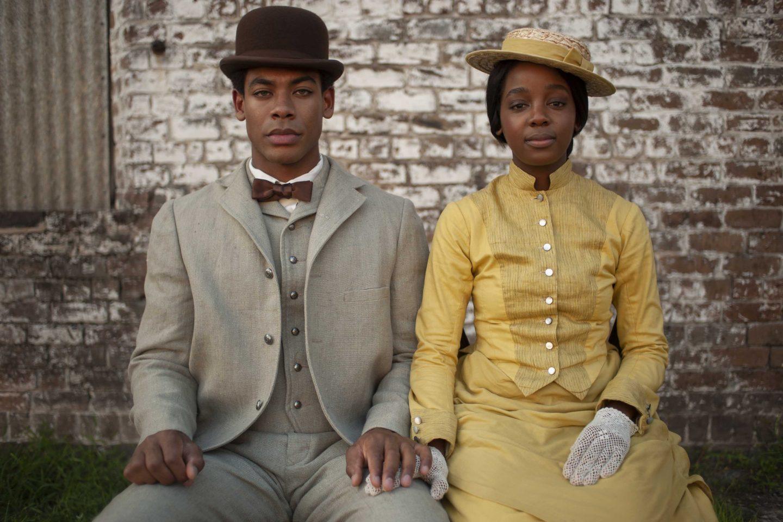 Cena da série The Underground Railroad. A cena mosta Caesar e Cora sentados, posando para a foto. Eles são jovens e negros. Ele é um homem de pele negra clara, olhos azuis e veste terno cinza e chapéu oval escuro. Ela tem a pele mais escuro e usa chapéu e vestido amarelos.
