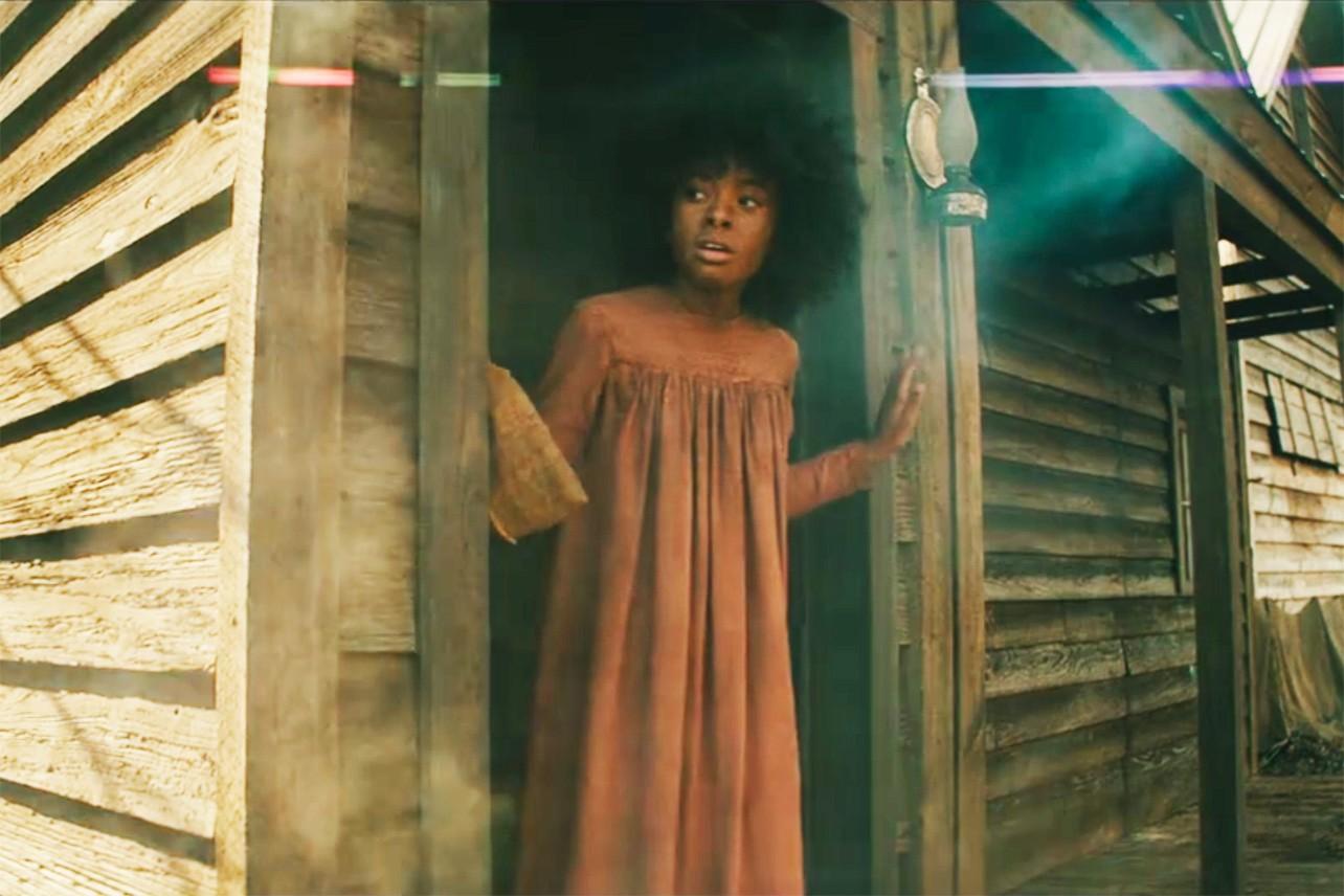 Cena da série The Underground Railroad. A cena mostra Grace, uma criança negra, com vestido vermelho e cabelo black power, olhando para fora, parada em uma porta.