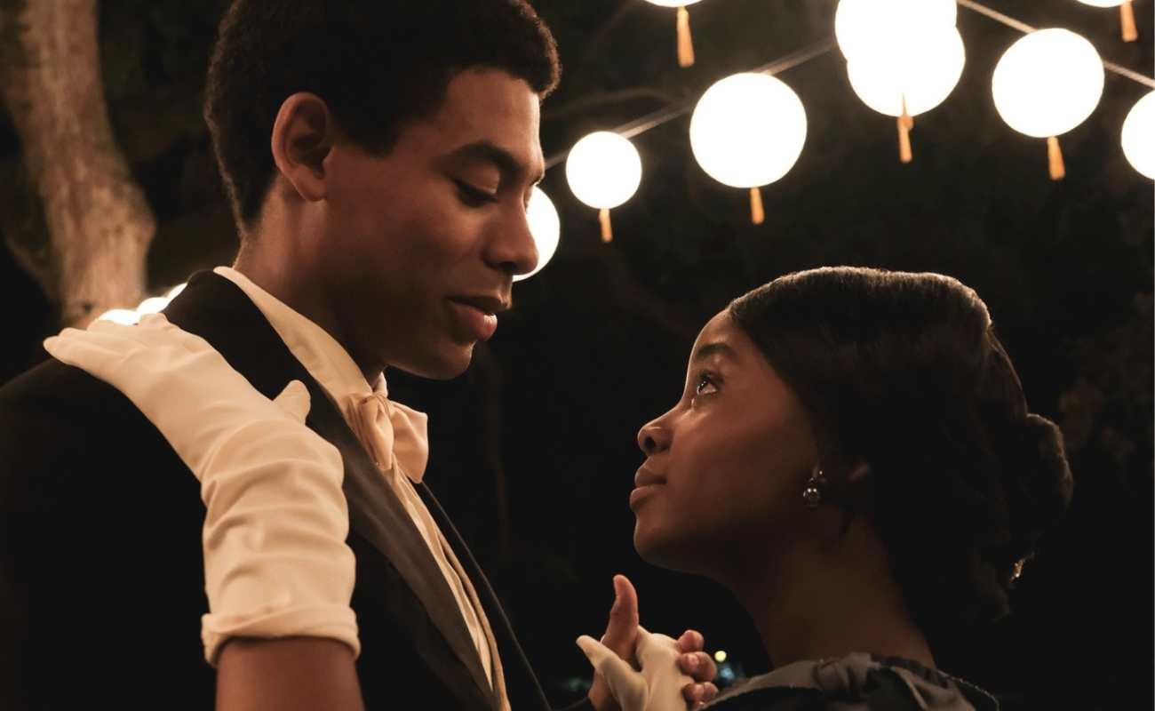 Cena da série The Underground Railroad. A cena mostra Cora e Caesar dançando. Eles são jovens e negros, ele usa terno e ela usa um vestido claro e luvas brancas. Eles se olham nos olhos.