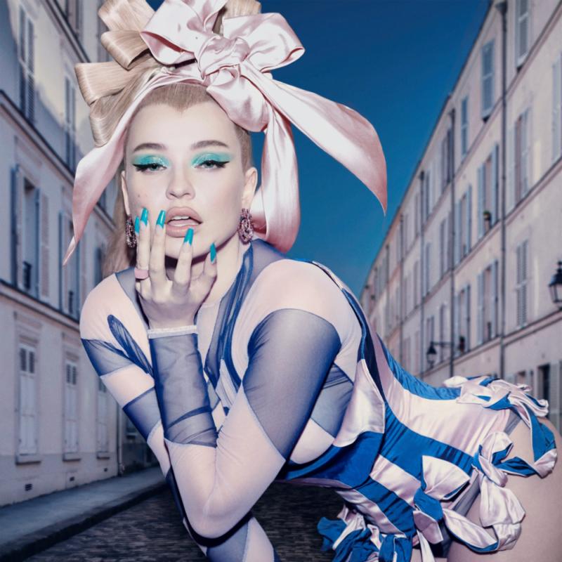 Capa da música Future Starts Now, da cantora Kim Petras. A foto mostra Kim, uma mulher branca e loira, inclinada para a frente, encarando a câmera. Ela tem uma fita rosa no cabelo, uma roupas na mesma cor, com faixas azuis e usa sombra azul nos olhos, além de ter unhas azuis e mão abaixo da boca.
