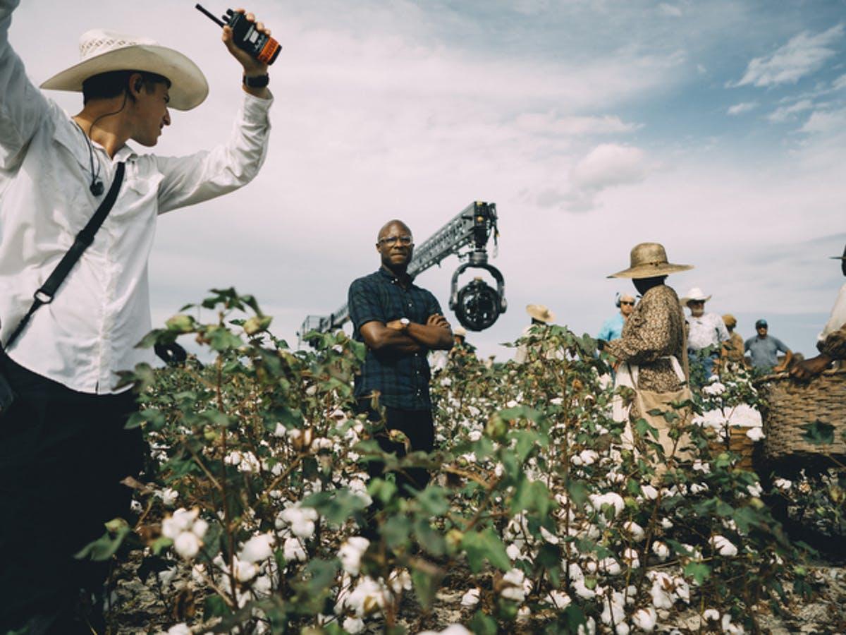 Cena dos bastidores de The Underground Railroad. A foto mostra o diretor Barry Jenkins, um homem negro de óculos, de pé em meio a uma plantação. Ao seu redor, vemos atores e pessoas operando as câmeras.