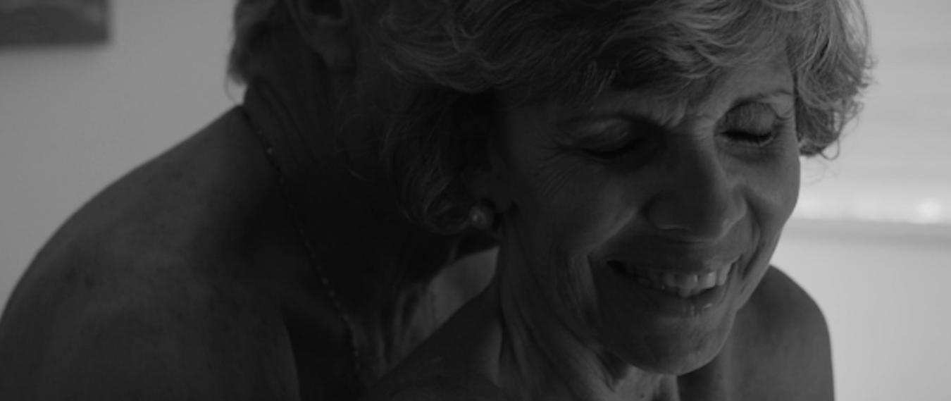 Cena do curta Acende a luz. Nela estão uma mulher e um homem de mais de 60 anos abraçado e nus. A mulher sorri. A imagem está em branco e preto.
