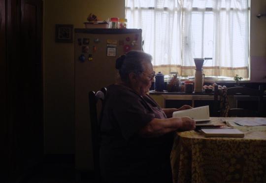 Cena do curta-metragem ngela. O cenário da é uma cozinha mal-iluminada em que, da esquerda para a direita, vemos um porta retrato pendurado na parede, uma geladeira com ímãs e potes em cima, uma janela com cortinas fechadas e uma pia com utensílios para fazer café. Ao centro no primeiro plano da foto, vemos a protagonista ngela, uma mulher que aparenta estar na casa dos sessenta anos, de cabelos brancos, usando um vestido marrom e óculos de grau, sentada à mesa lendo livros.