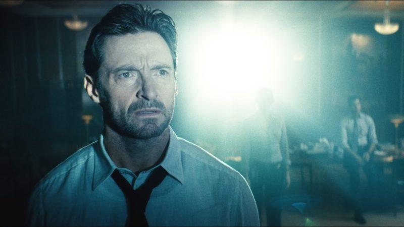 Cena do filme Caminhos da Memória. Vemos um homem branco observando a imagem de um projetor. Ele tem cabelo curto, barba por fazer e veste uma camisa branca com gravata. Ao fundo, vemos duas pessoas ofuscadas pela luz do projetor.
