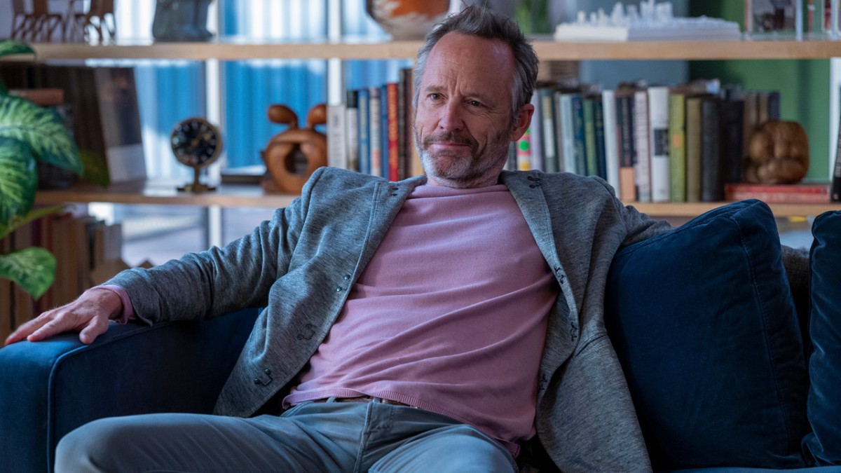 A imagem é uma cena da série In Treatment. Na imagem, John Benjamin Hickey, que interpreta Colin, está sentado em um sofá azul-marinho. Colin é um homem branco, de cabelo e barba grisalhos; ele veste uma camiseta rosa claro, um casaco cinza e calça jeans clara.
