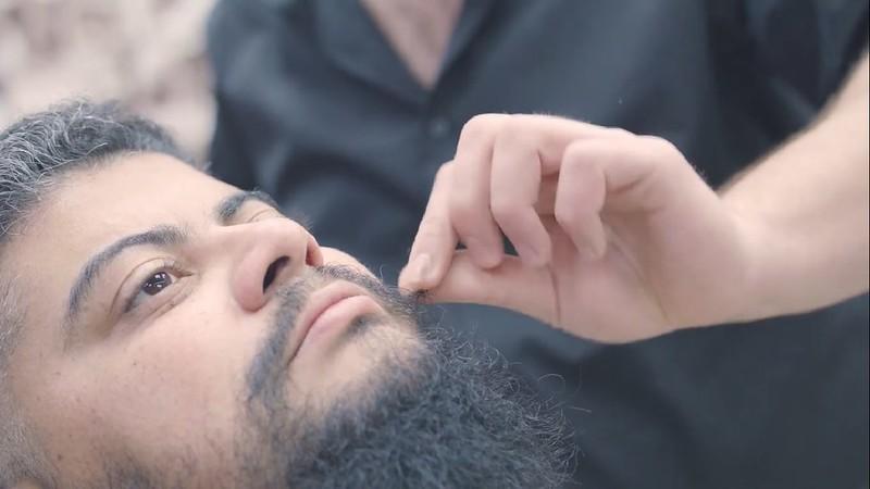 Cena do filme Eu, um outro. Com um enquadramento lateral, Raul Capistrano está deitado numa cadeira de barbeiro. Ele é um homem de cabelos curtos pretos acinzentados, barba e bigode compridos e olhos castanhos escuros. Ao seu lado, um pouco desfocado, está a parte superior até os ombros de um homem de camisa preta. Ele é branco e sua mão direita ajeita o bigode de Raul.