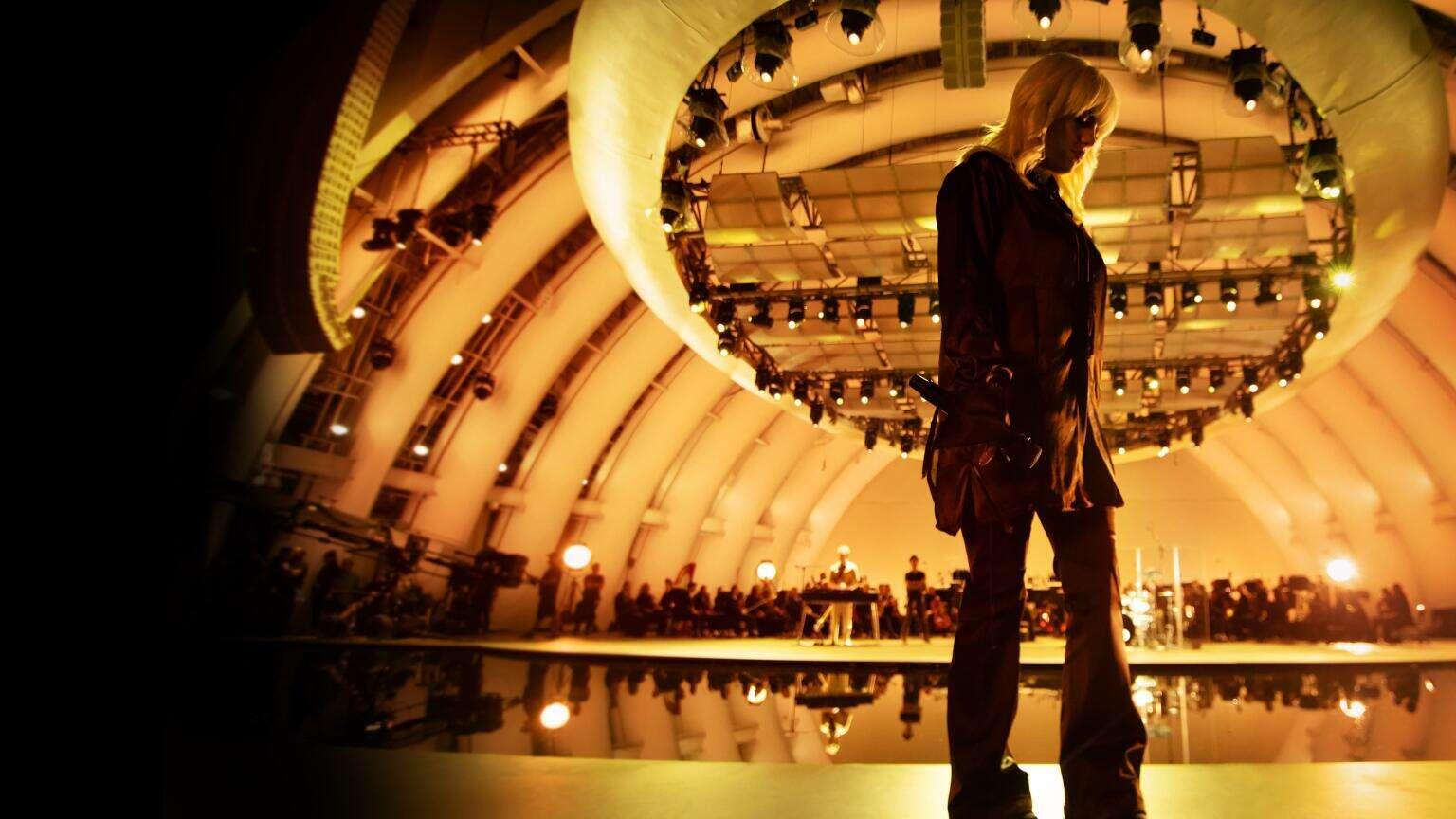 Foto do filme Happier Than Ever: Uma Carta de Amor Para Los Angeles - Uma experiência de Billie Eilish em concerto. A imagem mostra Billie Eilish, uma mulher jovem, de cabelo pintado de branco, vestindo roupas cor-de-vinho escuro, em pé, virada para a esquerda, com um microfone na mão paralela ao corpo. Ao fundo vemos uma orquestra em um palco em desfoque, e acima vários equipamentos de iluminação.