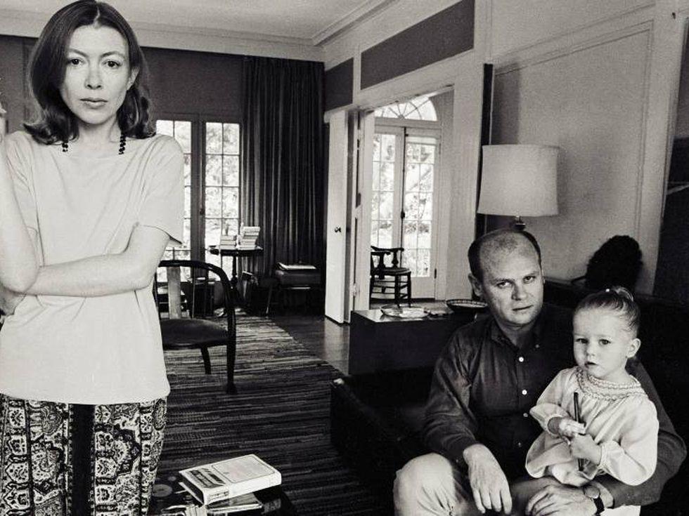 Fotografia de Joan e de sua família. A imagem está em preto e branco, Joan Didion está de pé na esquerda da foto, ela é uma mulher branca de cabelos e olhos castanhos, a autora está vestindo uma blusa clara e uma saia estampada. Seu marido, John Dunne, está sentado no sofá à direita da imagem, ele é um homem branco e parcialmente careca, o escritor veste uma blusa de botões escura e uma calça clara. Além disso, John também segura sua filha, Quintana Dunne, nos braços, a menina é loira e usa um vestido claro. O cenário é uma sala de estar, existindo esquadrias no fundo, chão de madeira e móveis compondo o ambiente.