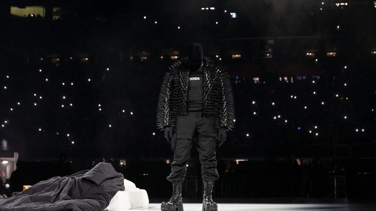 """Imagem retirada da segunda audição do álbum Donda. No centro, vemos Kanye West, homem negro, que tem seu corpo inteiramente coberto por roupas. Ele veste um colete preto com os dizeres """"Donda"""" no centro, e por cima jaqueta preta cheia de espinhos. Ainda usa uma calça, botas e luvas pretas. Seu rosto é inteiramente coberto por uma máscara preta. Ele se apresenta de pé, cabisbaixo, olhando para o chão. O cenário é noite, sendo Kanye iluminado apenas por um grande holofote de luz branca. Ao fundo, vê-se apenas vários flashes de celular ligados, acesos por uma grande plateia que se apresenta nas arquibancadas do estádio."""