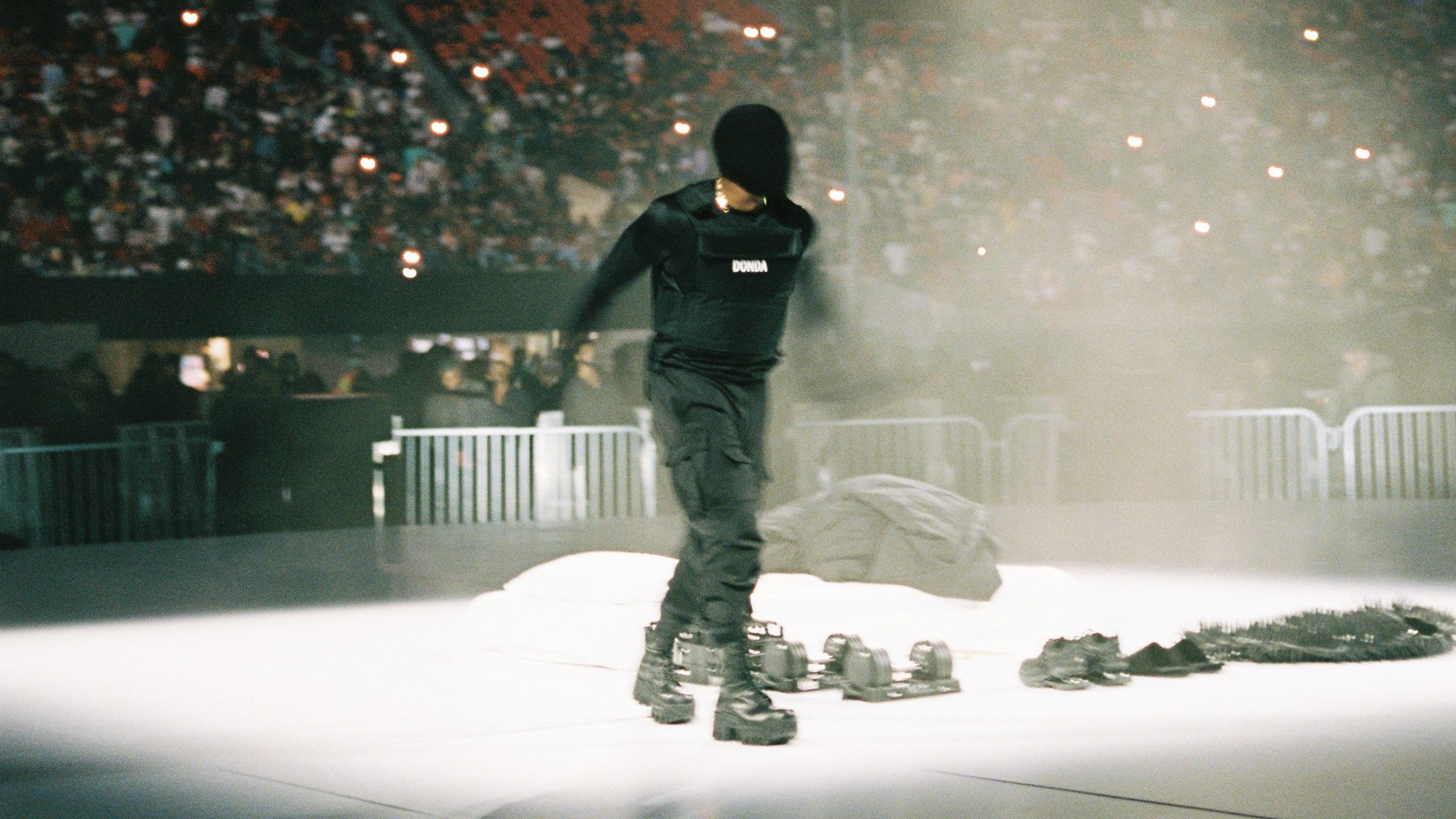 """Imagem retirada da segunda audição do álbum Donda. Nela, vemos, ao centro, Kanye West, um homem negro, que veste uma máscara preta, cobrindo todo o seu rosto. Ele ainda veste um colete preto, com os dizeres """"Donda"""" no centro, uma calça e botas de cano alto pretas. Ele anda para frente, e a câmera captura o momento específico em que ele se move, fazendo com que a imagem de seus braços fique ligeiramente borrada, dando sensação de movimento. O cenário é noite, e Kanye é iluminado pela luz branca de um holofote. A cena se passa em um estádio, e pode-se ver ao fundo um grande número de pessoas lotando as arquibancadas. Jogados ao chão, do lado de Kanye, pode-se ver um colchão branco, uma colcha preta, uma jaqueta preta, dois pares de sapatos pretos e dois pares de haltares."""