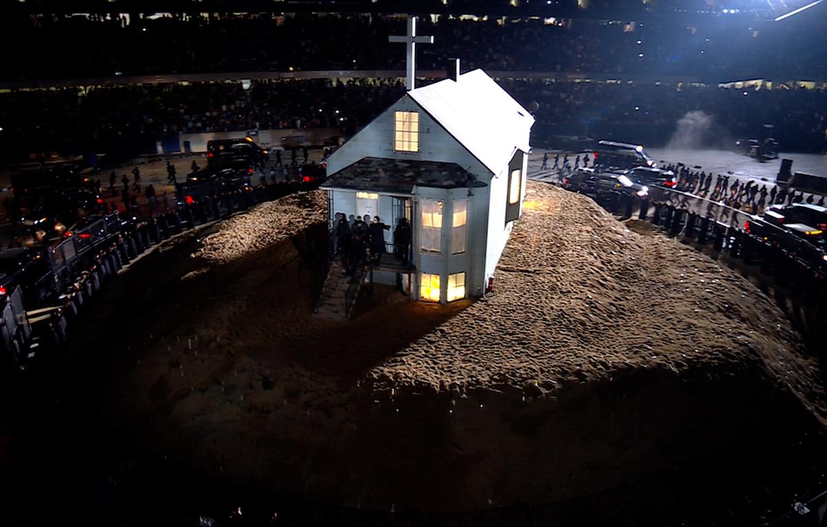 Imagem retirada da terceira audição do álbum Donda. Vemos, ao centro, uma casa simples, feita de madeira da cor branca, com uma cruz branca posicionada na ponta do telhado. Ela se apresenta no meio de um pequeno morro de terra. Na sacada da casa, pode-se ver um grupo de seis pessoas vestindo preto. Aos lados, um grande grupo de pessoas e carros rodeiam em círculo a casa. O cenário o de um estádio à noite noite, e pode ser visto ao fundo um grande grupo de pessoas lotando as arquibancadas
