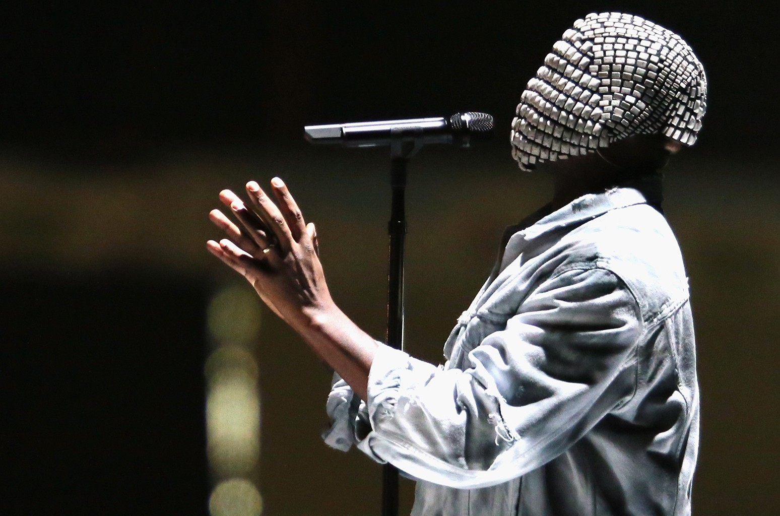Imagem retangular com o fundo desfocado. Vemos, de perfil, Kanye West, um homem negro vestindo uma jaqueta jeans cinza e usando, no rosto, uma máscara cravejada por lantejoulas pratas, que cobre inteiramente seu rosto. Ele tem um microfone, preso por um pedestal, apontado para a sua boca, e suas mãos estão levantadas na altura de seu peito. Sua cabeça está ligeiramente levantada para cima, como se ele interpretasse uma música.