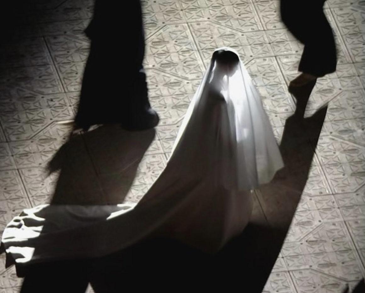 Imagem retirada da terceira audição do álbum Donda. No centro, vemos Kim Kardashian, uma mulher coberta totalmente por um grande véu branco. Através dele, pode-se ver sua silhueta, expondo seu cabelo trançado, preso por um rabo de cavalo. A visão que temos é de perfil, e ela anda para frente, com a cabeça ligeiramente baixa, enquanto um grupo de pessoas, vestindo preto, a rodeiam, andando no sentido contrário.