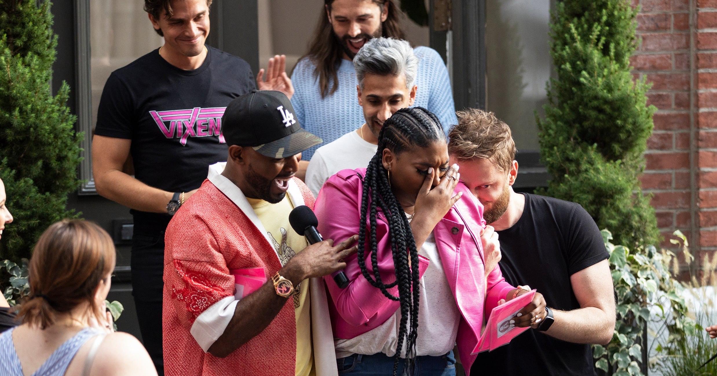 Cena da série Queer Eye. Na imagem estão Antoni, Tan e Jonathan mais atrás, e Karamo, Rihanna e Bobby mais a frente com os braços passados um em volta do outro. Ao fundo há portas de vidro, vasos de flor e uma parede de tijolos. Antoni é um homem branco de cabelos castanhos, usa uma camiseta preta com estampa rosa no peito e olha para Rihanna com uma expressão emocionada. À sua direita está Jonathan, uma pessoa não-binária branca de cabelos castanhos compridos e barba, usa uma blusa azul bebê e está com as mãos para o alto numa expressão de comemoração. Um pouco abaixo e ao centro está Tan, um homem asiático de cabelos cinzas em um topete, ele usa um suéter branco e está sorrindo enquanto olha ligeiramente para baixo. À esquerda de Tan e mais abaixo está Karamo, um homem negro de barba curta e boné preto na cabeça, ele veste uma camiseta amarelo bebe, um kimono salmon com gola e punho brancos, segura um microfone preto com a sua mão direita e está olhando para Rihanna e sorrindo. À direita dele está Rihanna, uma mulher negra com o cabelo preto trançado, ela usa uma blusa branca, jaqueta rosa pink e calça jeans, está segurando um cartão rosa e enxuga as lágrimas enquanto o lê. À direita dela está Bobby, um homem branco de cabelos loiros em topete e barba curta, ele usa uma camiseta preta e está com o rosto encostado no ombro de Rihanna enquanto segura seu braço.