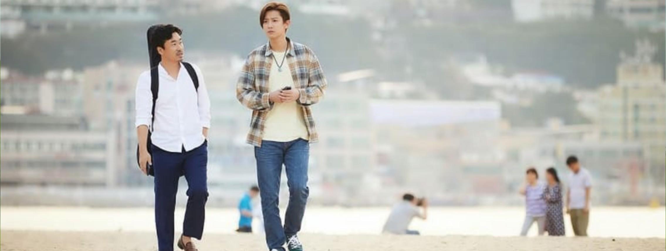 Cena do filme The Box - No Ritmo do Coração. Foto dos personagens Minsoo e Jihoon caminhando em uma praia. Minsoo, a esquerda, tem cabelos pretos curto e barba, carrega um violão nas costas e usa uma camisa social branca, calça azul escuro e um sapato social marrom. Ao seu lado direito, Jihoon, com cabelos castanhos e curto, ele usa um colar, uma camisa xadrez marrom e cinza por cima de uma camiseta branca, calça jeans e tênis azul. Ao fundo da imagem podemos ver uma pessoa tirando foto de outras, o mar e alguns prédios.