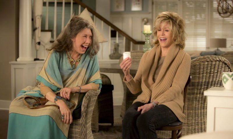Duas mulheres idosas estão sentadas em cadeiras dando risada. A mulher da esquerda tem cabelos grisalhos na altura do ombro, ela é branca, está usando um colar de pedras verdes, um vestido-túnica azul e amarelo claro, pulseiras de pedras azuis e anéis também de pedras. No seu colo segura uma pequena bolsa marrom e sua cadeira é feita de palha. A sua direita está uma mulher branca e loira de cabelos curtos, ela está usando um tricô bege com uma blusa bege escura por baixo e uma calça jeans preta, na sua mão direita está segurando uma caixa branca de comprimidos e na esquerda está usando um relógio prateado. Ao fundo temos uma mesa redonda com cadeira, um corrimão de madeira e uma janela branca.