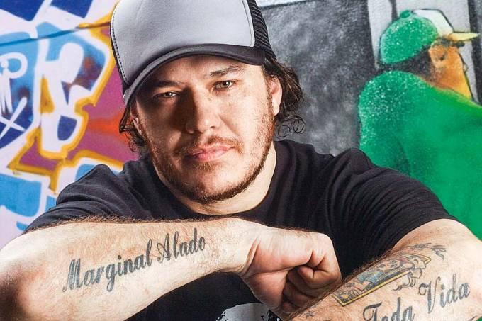 """Foto de Chorão. Ele, um homem branco, cruza os braços enquanto exibe as suas tatuagens. Uma delas escreve """"marginal alado"""", nome do documentário sobre sua vida."""