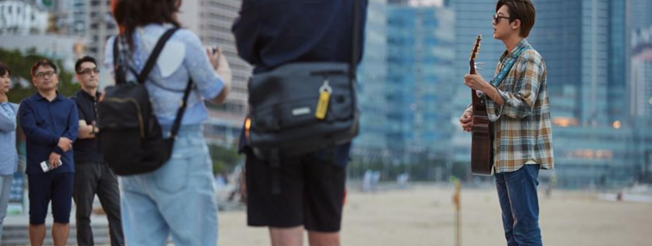 Cena do filme The Box - No Ritmo do Coração. Foto dos bastidores. Chanyeol está parado, tocando um violão e olhando para o público à esquerda da imagem, ele usa um óculos escuro, uma camisa xadrez laranja e cinza e uma calça jeans. Ao fundo pode-se ver a praia e alguns prédios.