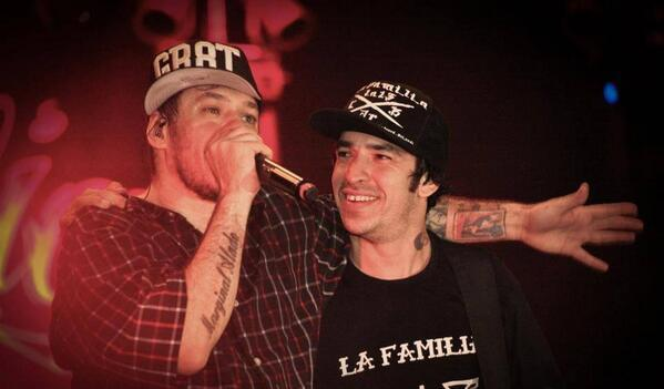 Foto de Chorão e Champignon no palco de um show. Ambos os homens são brancos e vestem bonés enquanto se abraçam. Chorão segura um microfone e Champignon estampa um sorriso.
