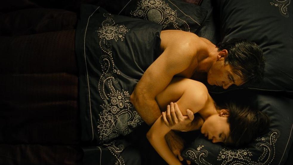 Cena do filme A Pele que Habito mostra um homem branco de cabelos curtos e castanhos e uma mulher branca, de cabelos curtos e castanhos, abraçados em uma cama. Ambos estão nus e cobertos com um lençol azul marinho.