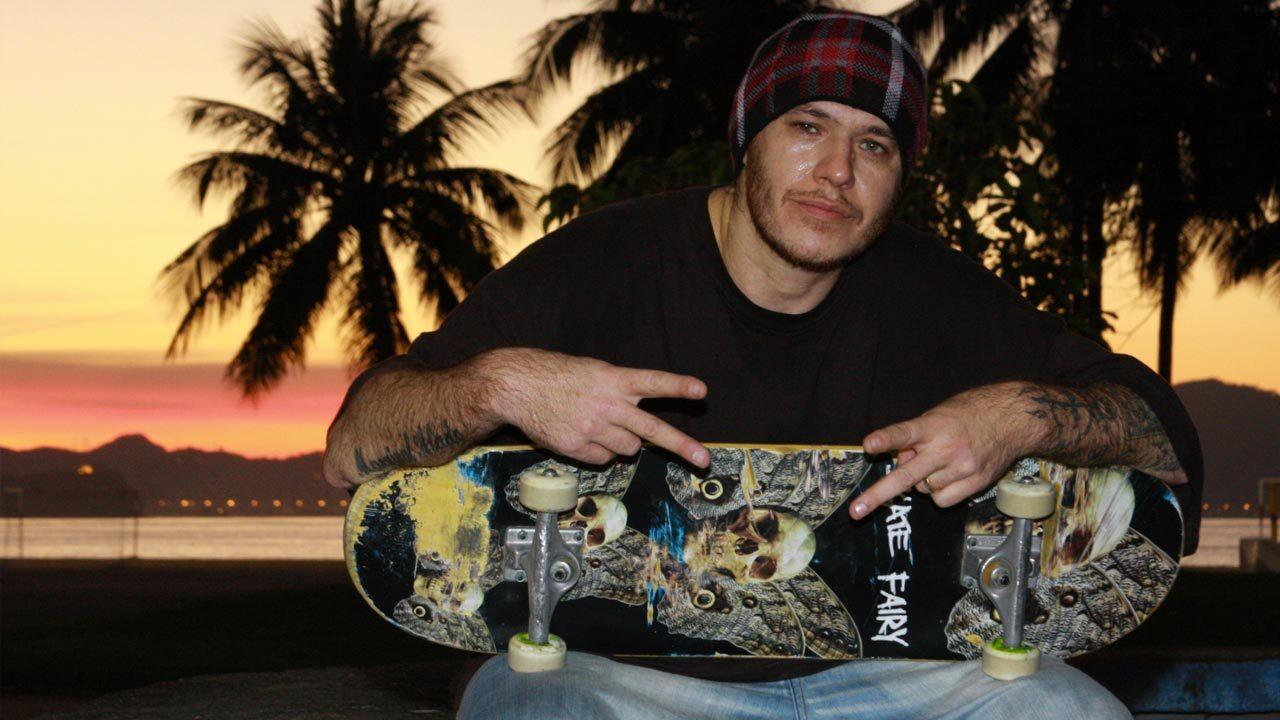 Foto de Chorão de costa para a praia e segurando um skate personalizado com a imagem de uma caveira. Ele, um homem branco, veste uma camisa preta, uma calça jeans azul clara e uma touca xadrez.
