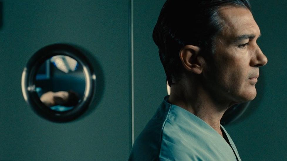 Cena do filme A Pele que Habito em que há um homem branco de cabelos curtos e castanhos de perfil, vestindo um jaleco de cirurgia. Ao fundo está uma porta de sala cirúrgica, em que se pode ver pelo vidro a imagem borrada de alguém deitado na maca.