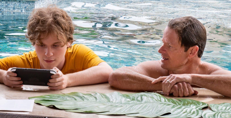 Cena da série The White Lotus. Na imagem, vemos dois hóspedes do resort. O da esquerda é um jovem loiro, de pele branca. Ele está vestindo uma camisa amarela, e segura um tablet nas duas mãos, enquanto olha pra ele. Na direita tem um homem mais velho, loiro e de pele clara, com os cabelos molhados, está sem camisa. Ambos estão dentro de uma piscina, apoiados na borda. Está de dia.