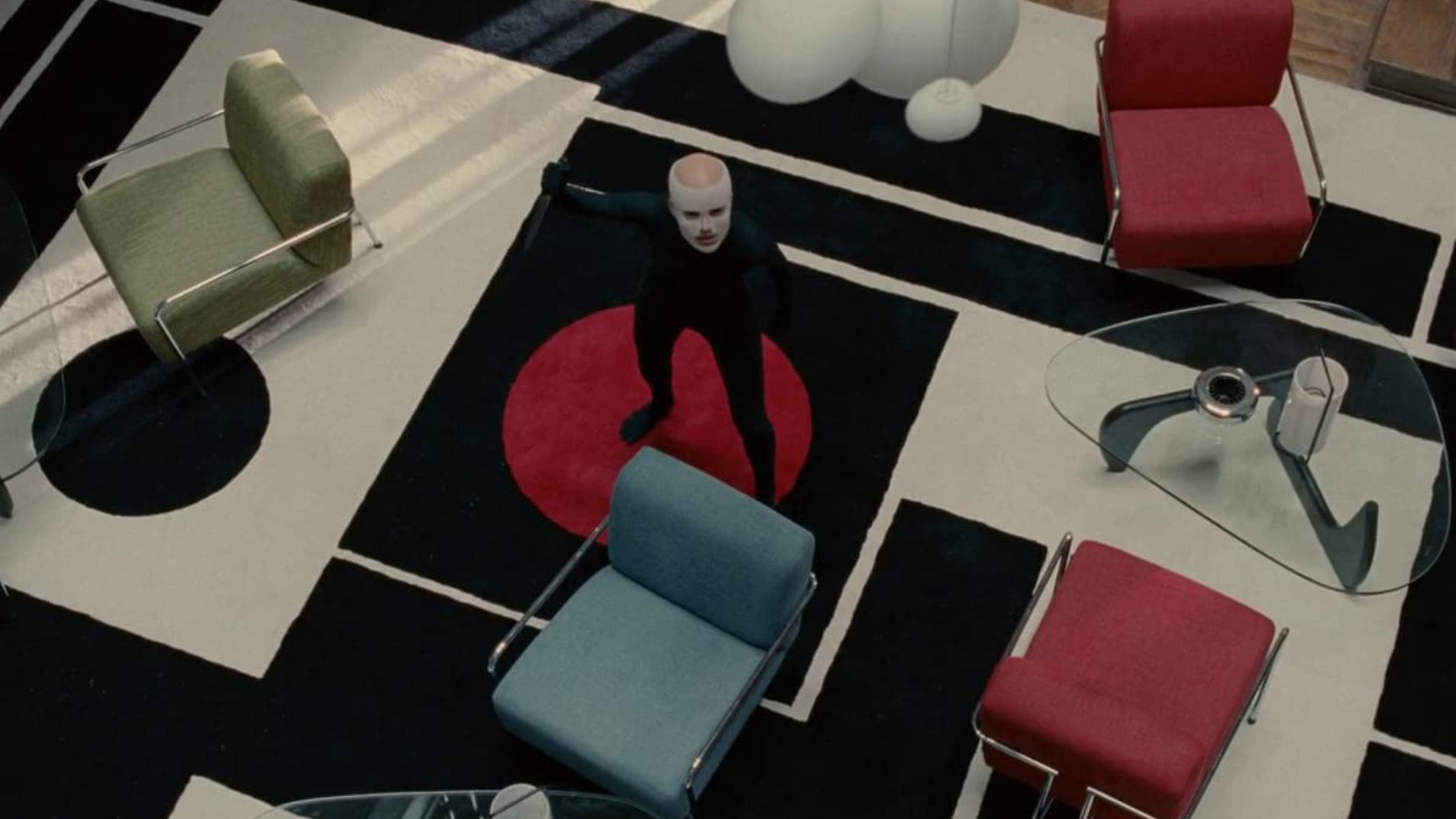 Cena do filme A Pele que Habito mostra uma mulher branca, careca, usando uma máscara branca de recuperação após fazer uma cirurgia plástica e um casaco preto ao centro de uma sala, com móveis modernistas.