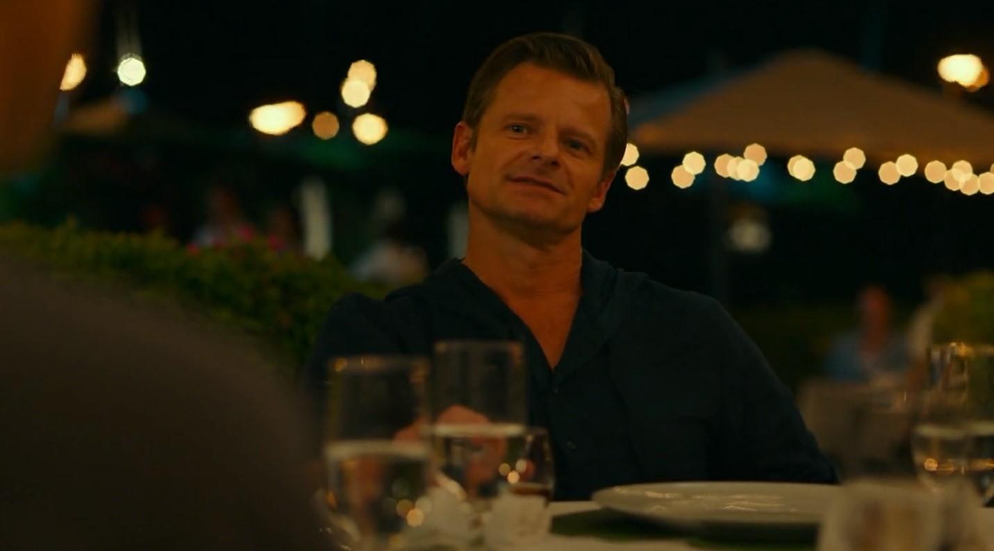 Cena da série The White Lotus. Na imagem, vemos um homem de cabelos claros, penteados de lado. Ele está sentado em uma mesa, com um prato branco e algumas taças de champagne à sua frente. Ele veste uma camisa azul marinho. Atrás dele, há algumas pequenas luzes. Ele está de frente, olhando para alguém, ao ar livre e está de noite.