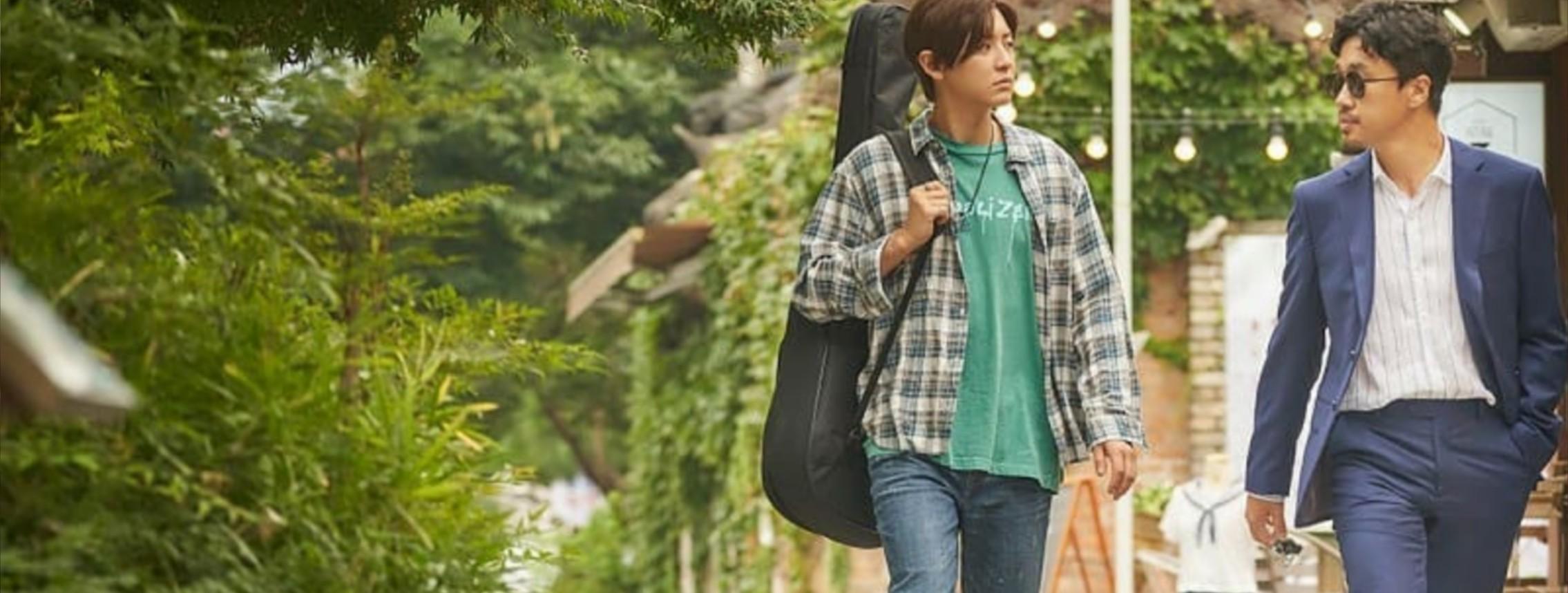 Cena do filme The Box - No Ritmo do Coração. Jihoon e Minsoo caminhando lado a lado. Jihoon, a esquerda está olhando para o horizonte à direita. Ele está usando uma camisa xadrez em tons de cinza com uma camiseta verde água por baixo e calça jeans, a alça de uma maleta para carregar violão está pendurada em seu ombro direito. Minsoo, a direita, está olhando para Jihoon. Ele está de óculos escuros, terno azul escuro e uma camiseta social branca. Ao fundo tem árvores, uma casa de tijolos e um manequim com um uniforme escolar.