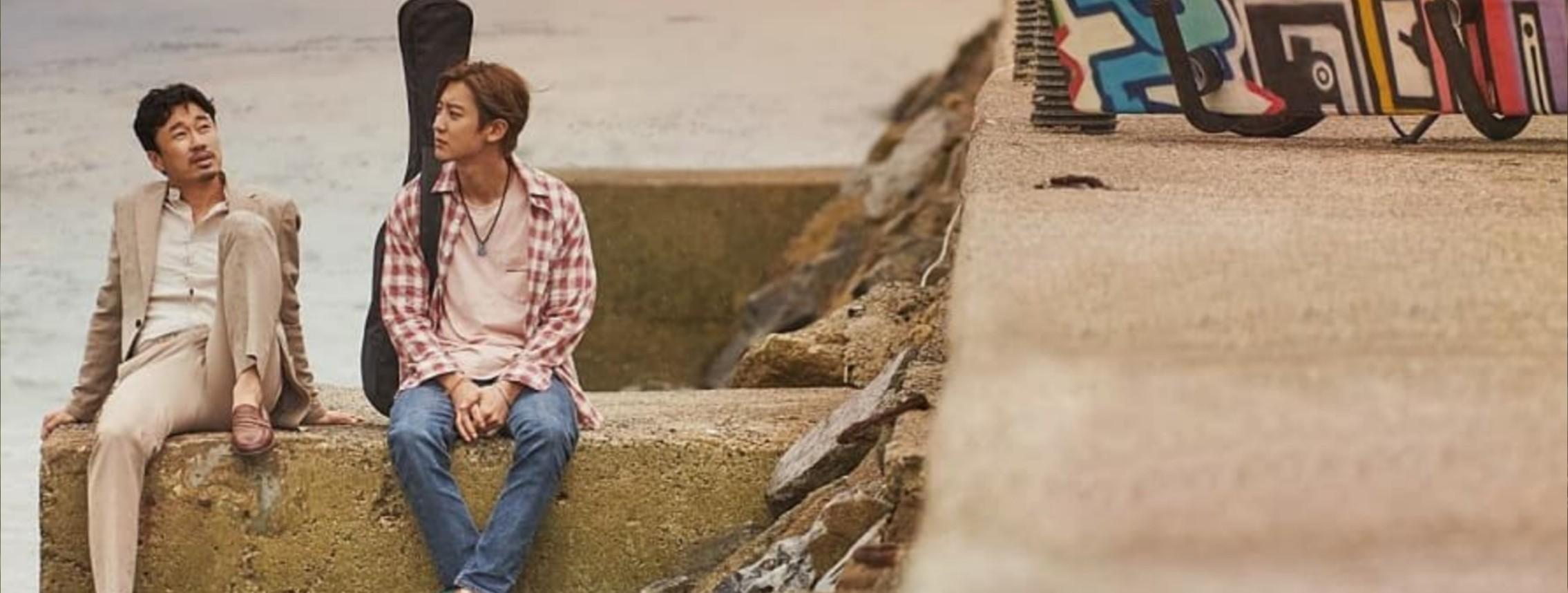 Minsoo e Jihoon estão sentados em uma sustentação de concreto em cima do mar. Minsoo, a esquerda, está com as mãos apoiando o corpo e o pé esquerdo em cima do concreto. Ele usa um terno bege, uma camisa social branca por baixo e um sapato social marrom. Jihoon, à direita, usa um colar, camisa xadrez branca e vermelha, uma camiseta branca por baixo, calça jeans e um tênis verde. Em seu ombro direito está pendurada a alça de um estojo de violão. Mais para a direita da imagem é possível ver uma estrada também de concreto e a caixa colorida que eles utilizam durante o filme. Ao fundo é possível ver o mar.