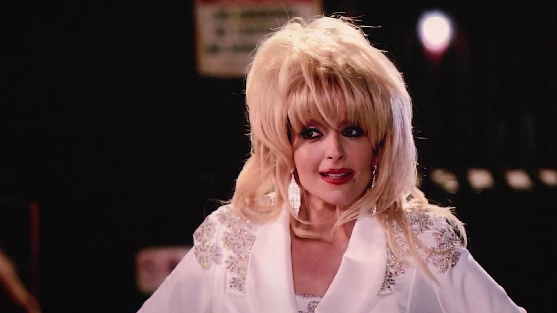 Cena da série Girls5eva. Em um ambiente interno, no centro da cena Tina Fey está caracterizada a fim de representar Dolly Parton. Ela é uma mulher branca de cabelos loiros, está com uma maquiagem escura e um batom vermelho, e na imagem só é possível vê-la do peito ao topo da cabeça. O fundo da imagem é escuro e desfocado.