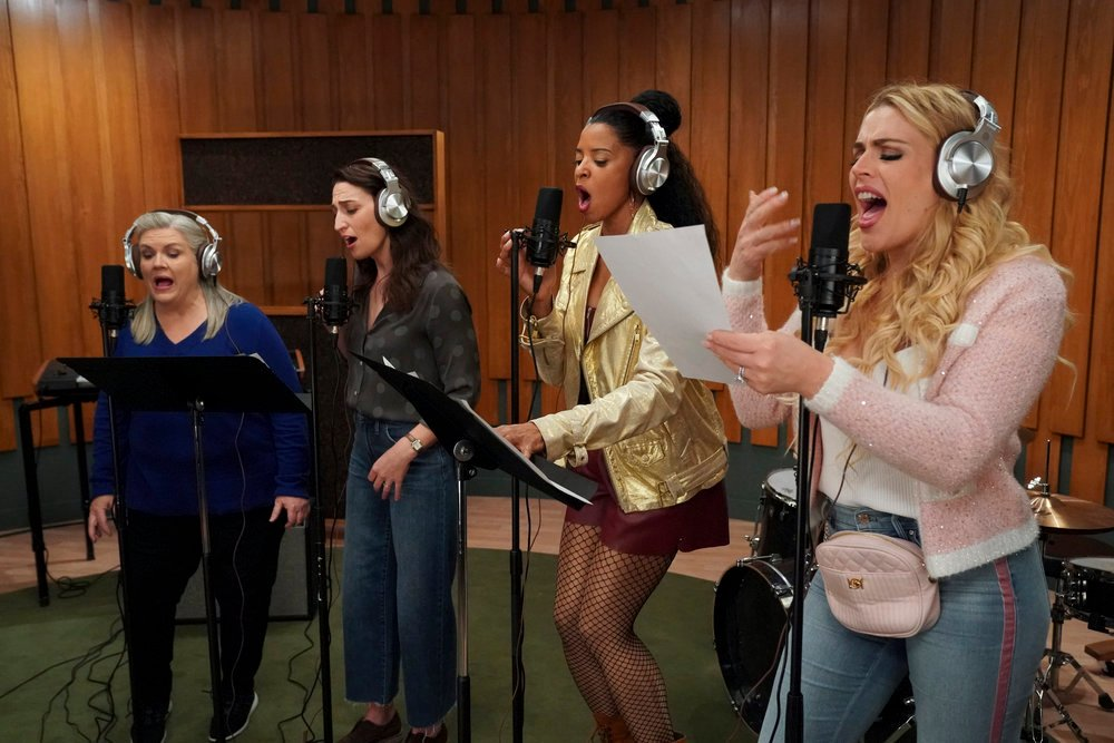 Cena da série Girls5eva. Em um estúdio de gravação quatro mulheres posicionadas em perspectiva e na diagonal estão gravando uma música. Gloria é uma mulher branca de cabelos brancos, ela está em pé diante de um microfone e um suporte de partitura para o qual ela está olhando, ela usa o headphone prata. A sua direita está Dawn, uma mulher branca de cabelos castanhos na altura dos ombros, ela está diante de um microfone e seu olhar está direcionado para o mesmo suporte de partitura, ela também usa um headphone prata. Ao seu lado está Wickie, uma mulher negra de cabelos pretos presos em um meio coque, com uma das mãos ela está segurando o microfone em frente a boca, enquanto a outra segura a letra na música apoiada no suporte, ela está com uma jaqueta dourada e meias arrastão, ela também usa um headphone prata. A sua direita, Summer, uma mulher branca, loira de cabelos ondulados, está segurando uma folha de papel branco em sua mão esquerda enquanto gesticula com a mão direita, ela está usando um headphone prata. Ao fundo da imagem, a parede do estúdio é de madeira clara e o chão é de carpete verde.
