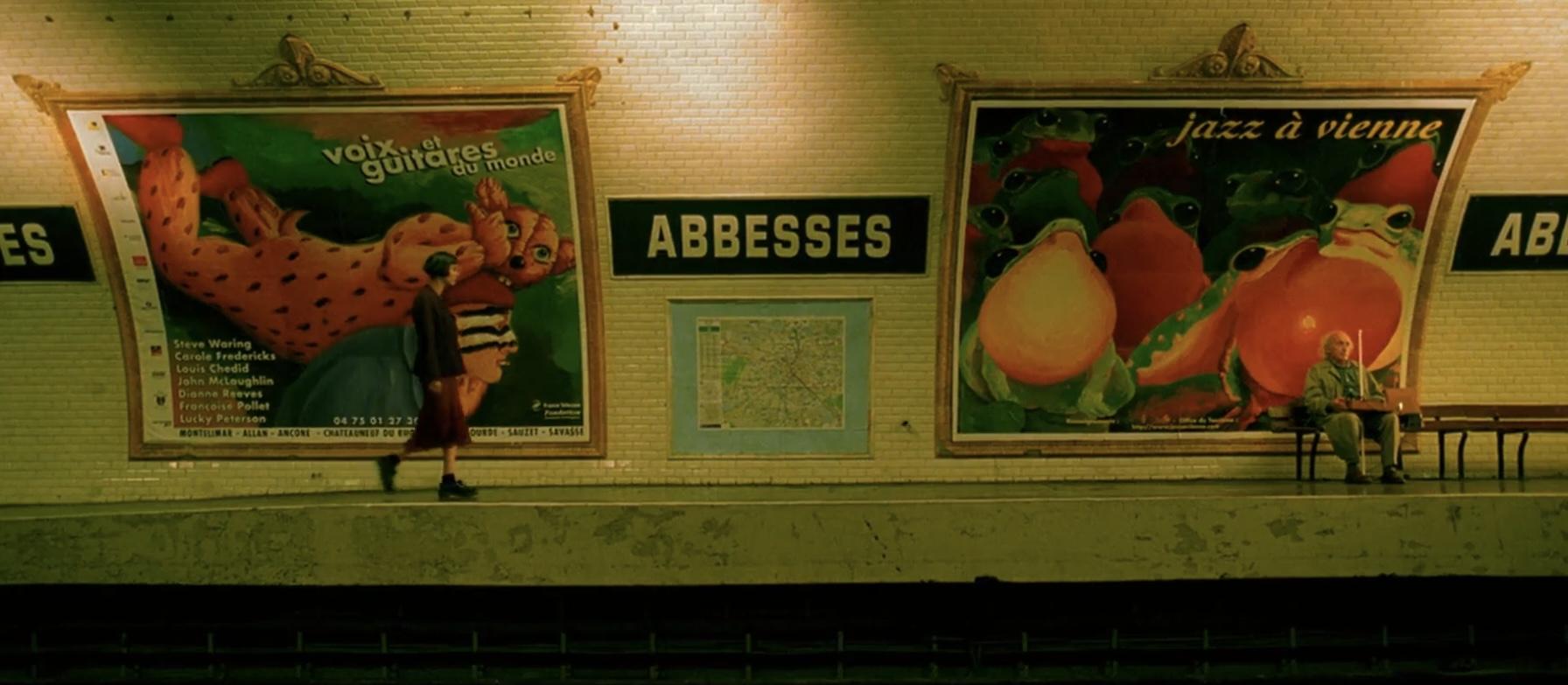 """Cena do filme O Fabuloso Destino de Amélie Poulain. A imagem mostra a personagem de Amélie caminhando por uma estação de metrô, vista de longe e de perfil. A câmera está nos trilhos, capturando as paredes da área de embarque, que é preenchida por anúncios coloridos do lado esquerdo e direito, e no centro existe uma placa escrito """"ABESSES"""". Amélie está do lado esquerdo, usando um vestido vermelho e botas pretas."""