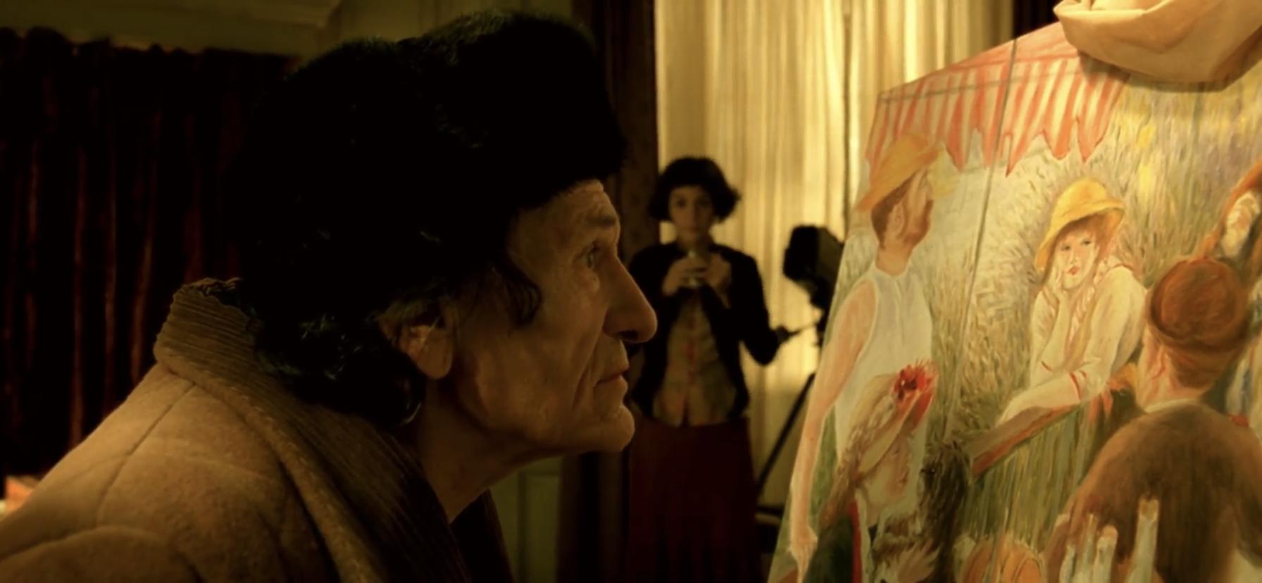 Cena do filme O Fabuloso Destino de Amélie Poulain. A imagem mostra um senhor de idade contemplando uma pintura, de perfil, e Amélie desfocada no meio, ao fundo. Do lado esquerdo da imagem, o senhor observa a pintura do lado direito. Ele é um homem branco, de cabelos pretos ondulados, e usa um casaco marrom. A pintura, que também aparece de perfil, mostra um grupo de pessoas no campo, com destaque para uma mulher ao centro, que usa um chapéu amarelo e olha para fora da imagem. No meio, em desfoque, Amélie segura uma xícara com as duas mãos e observa o senhor.