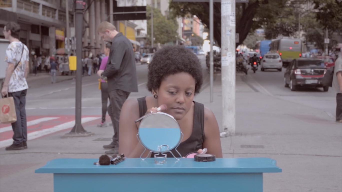 Cena do curta Minha Raiz. Nela há uma mulher negra ao centro, ela está sentada se maquiando em frente a um espelho redondo. O espelho está sob uma mesa azul, nela se encontram alguns itens de maquiagem também. A moça está em uma avenida movimentada,ao fundo se encontram pessoas esperando para atravessar a rua e carros, motos e ônibus passando.