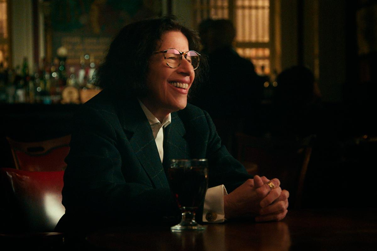 Cena de Faz de Conta que Nova York é uma Cidade exibe uma mulher idosa sentada à mesa de um bar, que aparece desfocado ao fundo. Ela tem cabelo comprido, ondulado e poucas rugas no rosto. Usa um óculos redondo e veste uma camisa branca com paletó de cor escura. Ela sorri. Ao seu lado, há um copo com bebida.