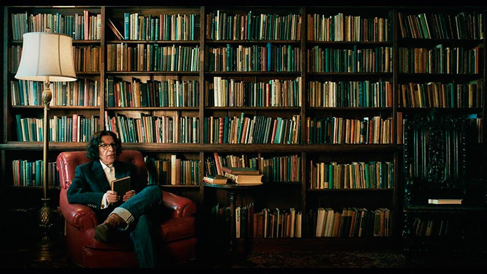Cena da série Faz de Conta que Nova York é uma Cidade exibe uma mulher idosa sentada em uma poltrona vermelha de sua biblioteca pessoal. Ela tem cabelo longo, ondulado e tem poucas rugas no rosto. Usa óculos redondo. Veste uma camisa branca com paletó de cor escura e uma calça jeans. Ela está sentada de pernas cruzadas e está com um livro na mão. No lado esquerdo, vemos um abajur e, do lado direito, vemos uma mesinha com livros em cima. Atrás dela, uma estante repleta de livros cobre a parede.