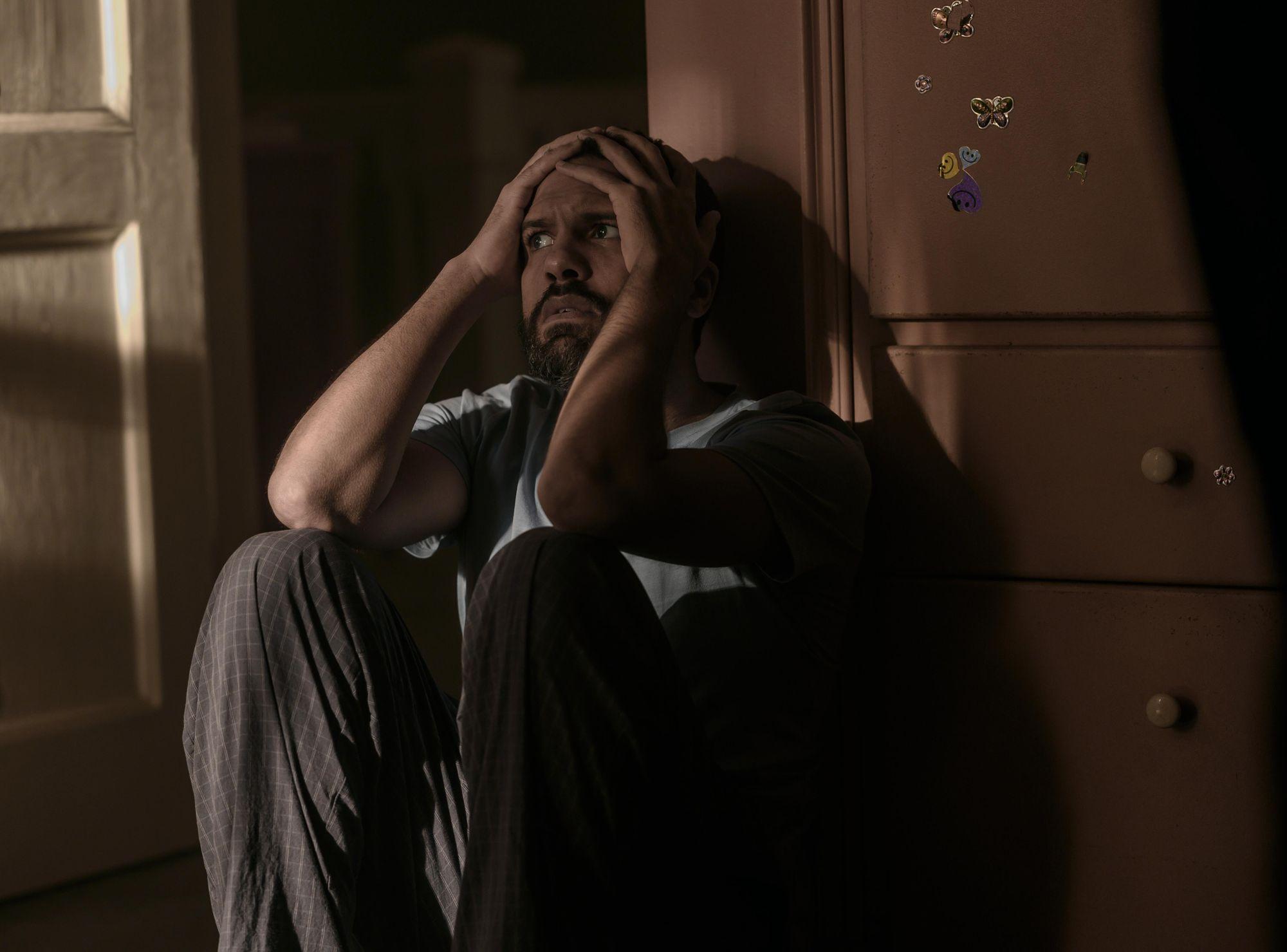 Cena de The Handmaid's Tale. O-T Fagbenle está sentado no chão, com as mãos na cabeça e uma expressão assustada. Ele é um homem negro de aproximadamente 35 anos. Está apoiado na parede e usa camisa azul e caça preta.