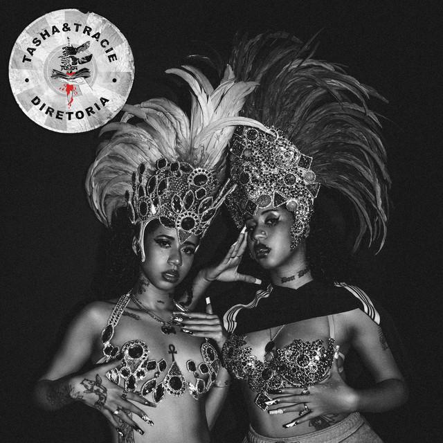 """Capa de Diretoria. A arte quadrada tem a foto de duas meninas gêmeas, que são negras e tem cabelo cacheado. Ambas vestem roupas de desfile de carnaval, com enfeites grandes na cabeça. O fundo é liso e a imagem está em preto e branco. No canto superior esquerdo está um circulo cinza com o texto """"Tasha e Tracie"""" e """"Diretoria"""" escritos em preto. No centro do círculo tem ainda o desenho de uma espada com sangue escorrendo."""