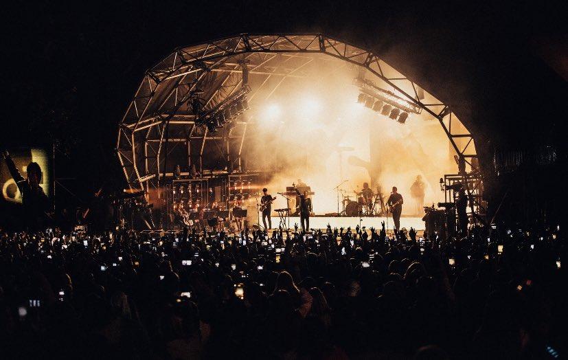 Imagem do palco do festival The Away From Home Festival. Mostra o cantor Louis Tomlinson e sua banda em cima de um palco em formato de semicírculo iluminado por luzes amarelas. Há bastante fumaça no palco. A frente, vemos uma multidão com muitas luzes de celulares aparecendo.