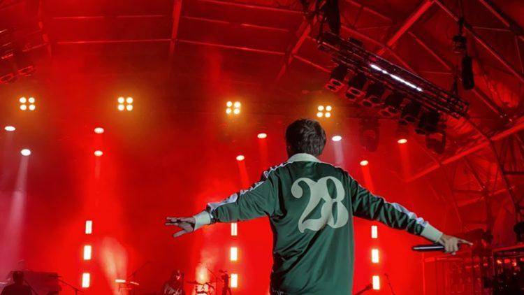 Imagem do cantor Louis Tomlinson no palco. A imagem mostra um homem branco, de cabelos lisos, castanhos e curtos, de costas para a câmera; Ele tem os braços abertos e usa uma camiseta verde de mangas cumpridas, que têm sua gola, punhos e uma lista em seus braços em branco. Vemos o número 28 estampado em branco nas costas. Ele segura um microfone com a mão direita. Ao fundo vemos alguns elementos do palco e uma luz vermelha intensa.