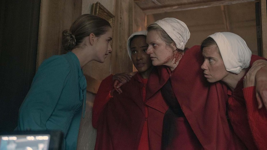 Cena da série The Handmaid's Tale. A cena mostra Mckenna Grace, uma jovem branca com roupas verdes de Esposa, falando com June, uma loira, branca, aia, de vermelho e manchada de sangue no pescoço. June é carregada por outras aias, vestidas de vermelho e com a touca branca na cabeça.
