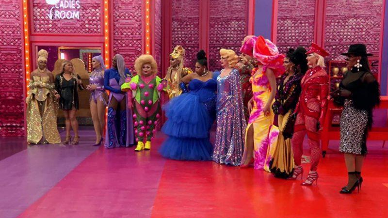 Cena de RuPaul's Drag Race All Stars apresenta as treze participantes montadas e enfileiradas uma ao lado da outra. O ambiente em que elas estão possui paredes rosa, chão listrado de lilás, laranja e magenta e luz de led.