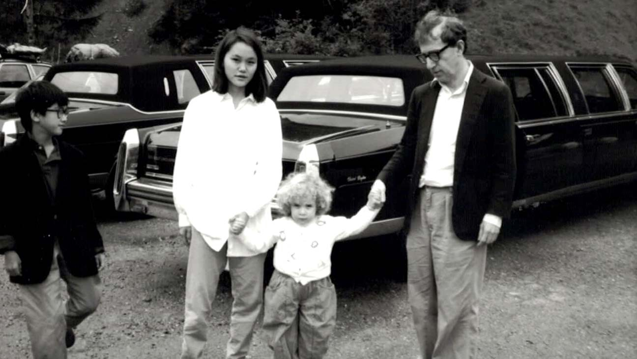 A imagem é uma foto de Moses Farrow, Soon-Yi Previn e Woody Allen, que estão de mãos dadas com Dylan Farrow.