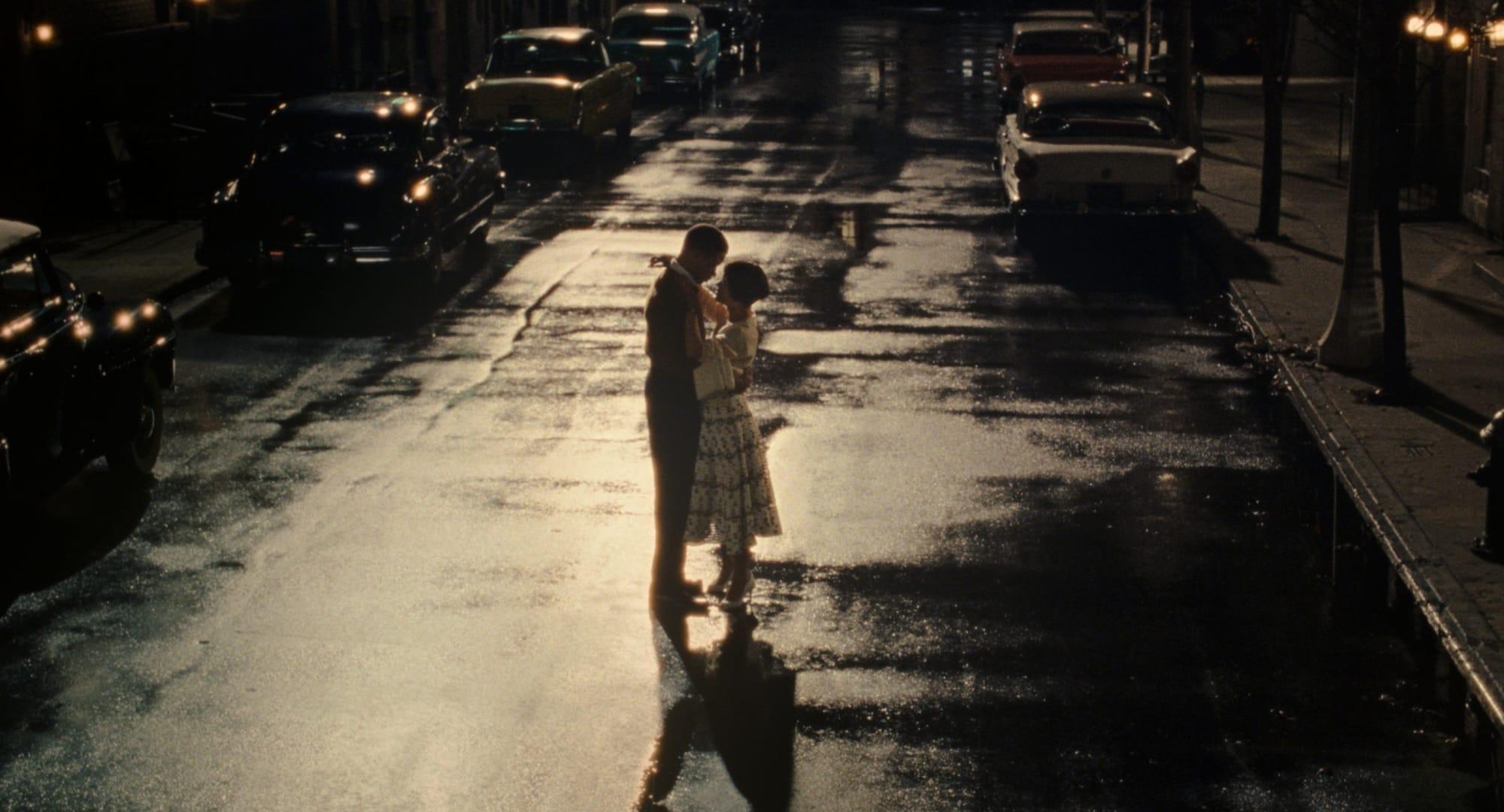 Cena do filme O Amor de Sylvie. A foto mostra uma mulher e um homem jovens e negros, em pé de frente um para o outro com os corpos próximos e com as mãos juntas, no meio de uma rua à noite com vários carros estacionados próximos da calçada. Eles vestem roupas da década de 50.