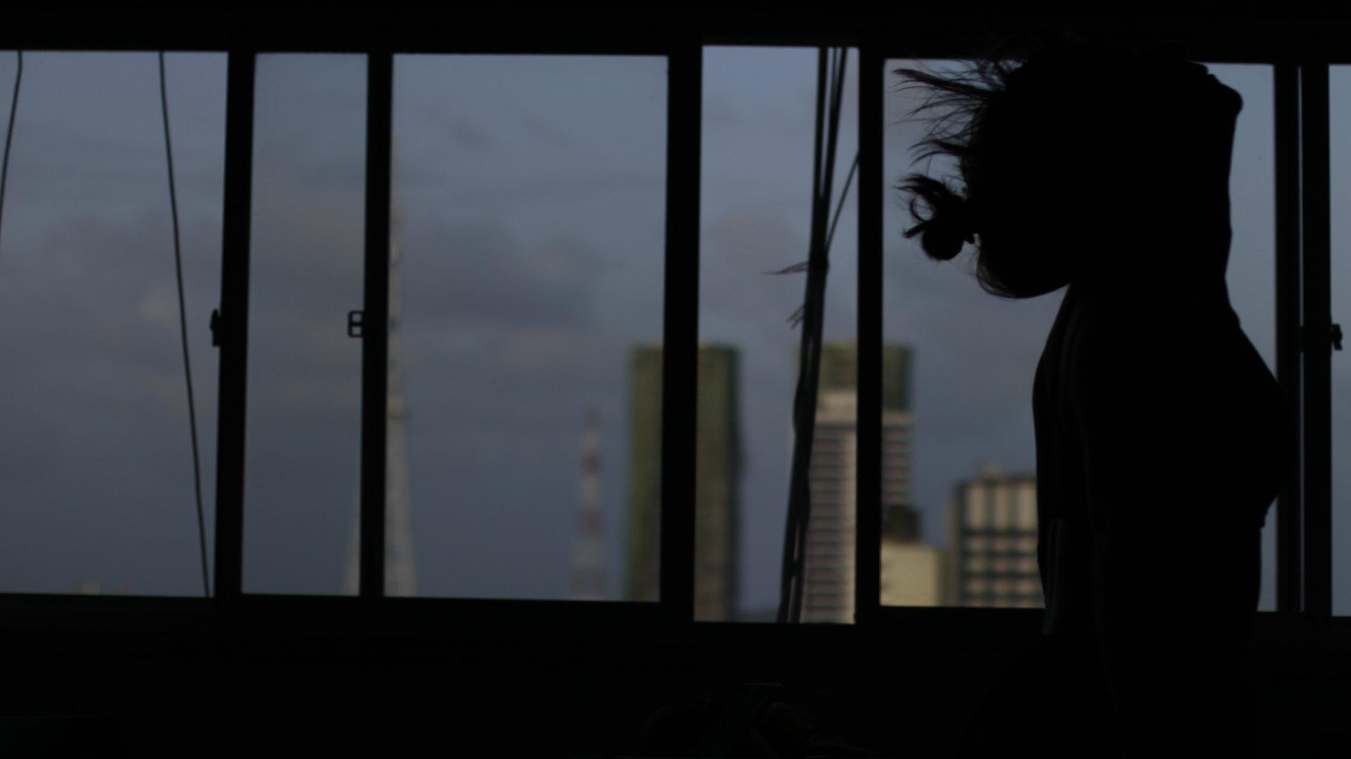 Cena do filme As flores que guardei pra você. No lado direito da imagem é possível ver a silhueta de Ju, uma mulher ainda jovem. Ela está de perfil, sua cabeça está inclinada para cima, seus cabelos são lisos e ela usa um coque frouxo. Atrás de si há uma grande janela com vista para parte de alguns prédios da cidade e o céu de um início de anoitecer.