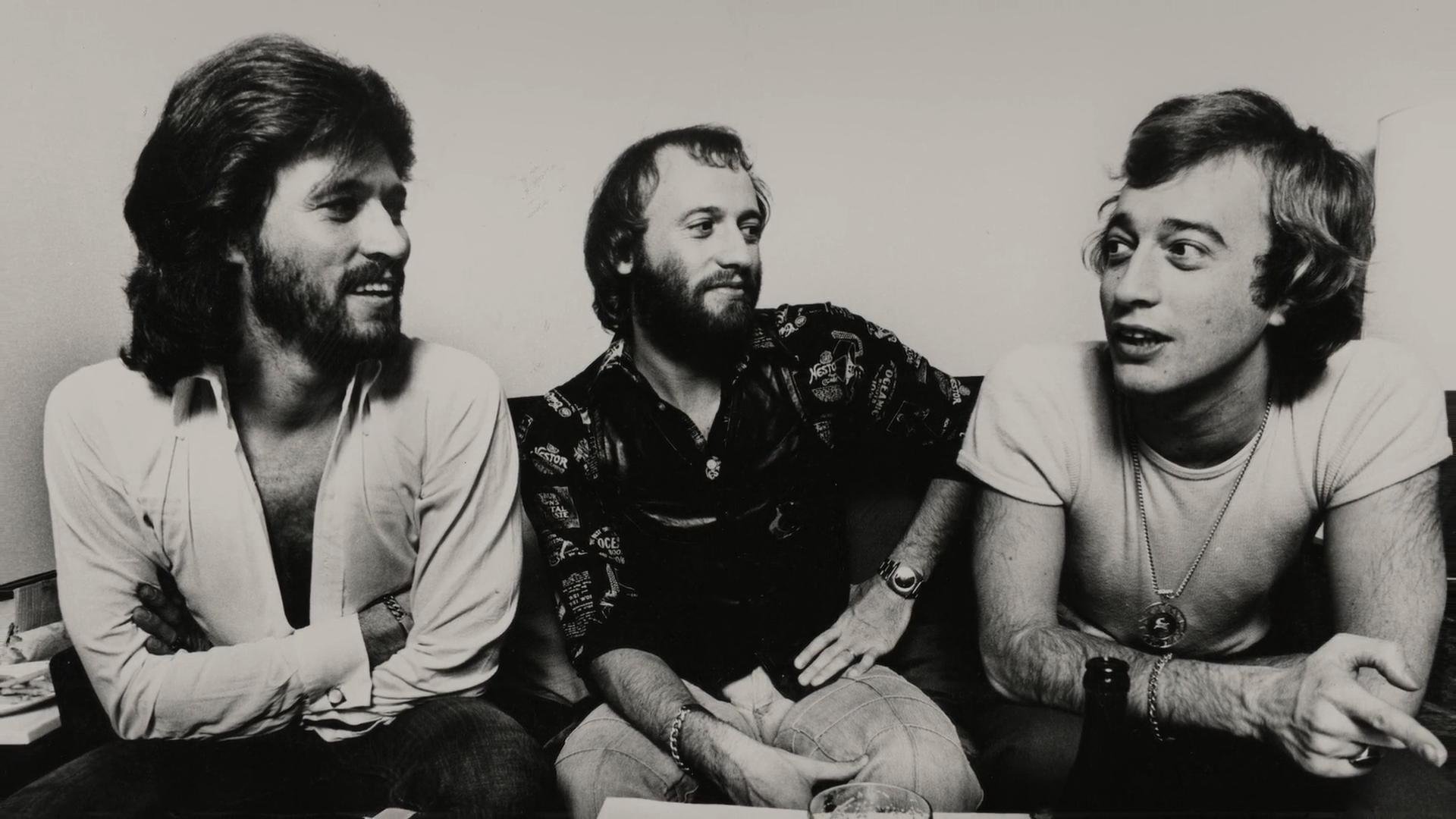 Cena do filme The Bee Gees: How Can You Mend A Broken Heart. A imagem mostra uma fotografia em preto e branco dos três irmãos Gibb sentados, se olhando, enquanto conversam. Primeiro, à esquerda, está Barry Gibb, uma homem branco, de cabelos lisos na altura do ombro e barba cheia. Ele veste uma camisa branca desabotoada até o peito e está de braços cruzados, olhando para Robin, que está no lado direito. Ele também é um homem branco, tem cabelos curtos lisos e veste uma camiseta clara e colares longos no pescoço, apoia os cotovelos nos joelhos e olha para Barry de volta, conversando com o irmão. No meio, está Maurice Gibb, também um homem branco, de cabelos médios e barba cheia, que veste uma camisa estampada. Ele também olha para a direita, onde está Robin, e está com a mão esquerda na cintura e a mão direita segura a perna esquerda. Na frente do trio, aparece um pedaço de uma mesa, com copos e garrafas de bebidas. Eles estão sentados num sofá preto na frente de uma parede lisa e clara.