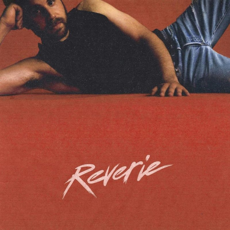 Capa do disco Reverie. Na foto, o artista Ben Platt está deitado na lateral, com a mão apoiando a cabeça. Ele é um homem branco com barba castanha, veste uma camiseta regata preta e uma calça jeans azul. O chão é laranja, e na parte inferior está escrito Reverie em fonte de cor branca.