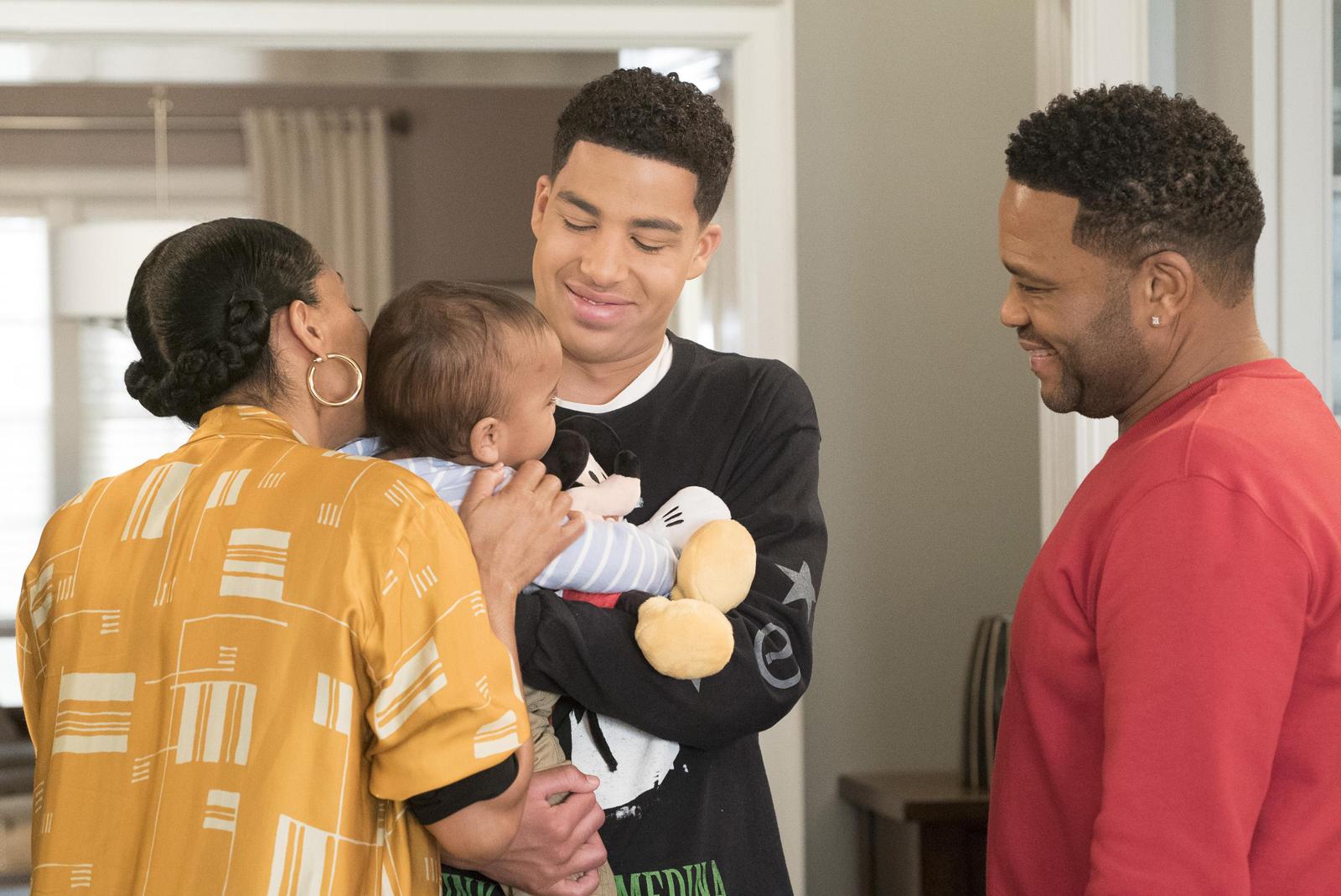 Cena de black-ish. Nela está um garoto negro vestindo blusa preta segurando um bebe no colo, olhando e sorrindo para este. Ao seu lado esquerdo, uma mulher negra com o cabelo preso em tranças e uma blusa amarela beija a cabeça do bebê. Na direita um homem negro de blusa vermelha olha para os três com um sorriso no rosto.